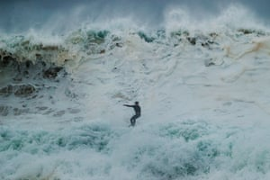 Sydney, Australia. A surfer rides a wave at South Narrabeen as Sydney braces for heavy winds