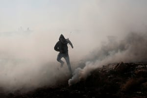 A Palestinian demonstrator runs away from teargas fired by Israeli forces during a protest against Israeli settlements in Deir Jarir.