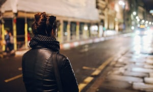 Young woman walking alone on the streets of London at night