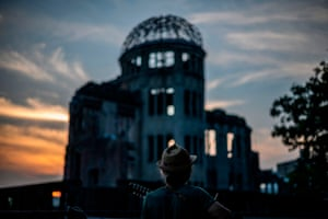 A man plays a guitar in front of the Atomic Bomb Dome