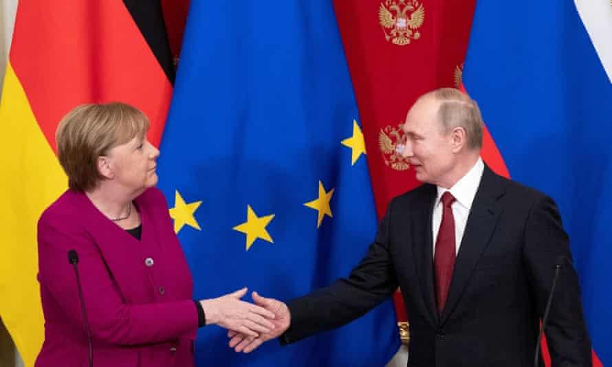 Angela Merkel and Vladimir Putin shake hands.