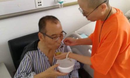 Liu Xiaobo  is fed to by his wife, Liu Xia, in a hospital in China.
