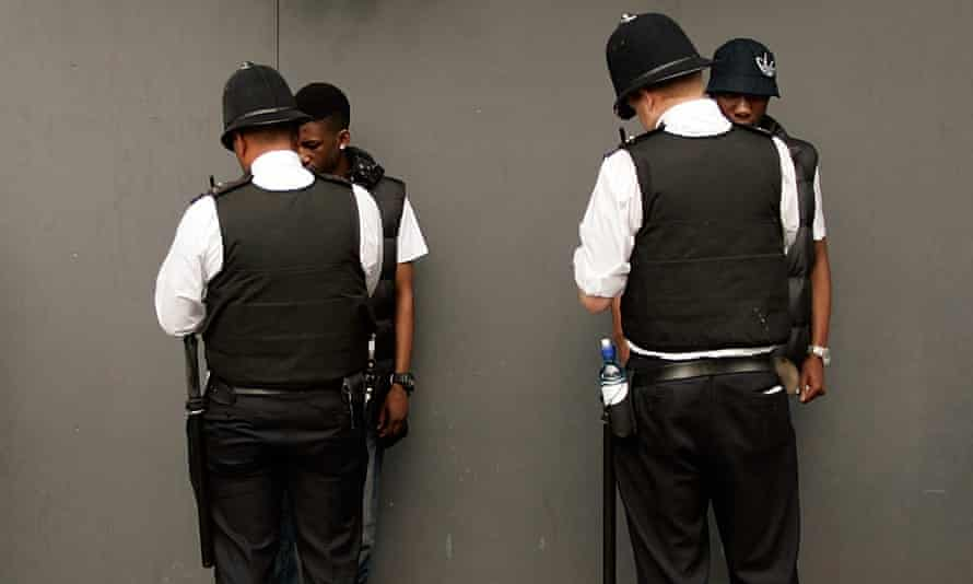 Two young black men being stopped and searched by police officers.
