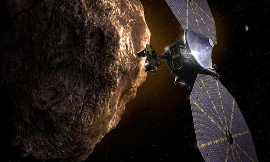 An artist's impression of Nasa's Lucy spacecraft flying past an asteroid in the orbit of Jupiter
