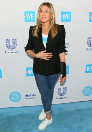 Jennifer Aniston shows how to nail white trainers with jeans and a blazer.