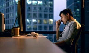 Office worker sitting alone at their desk at night.