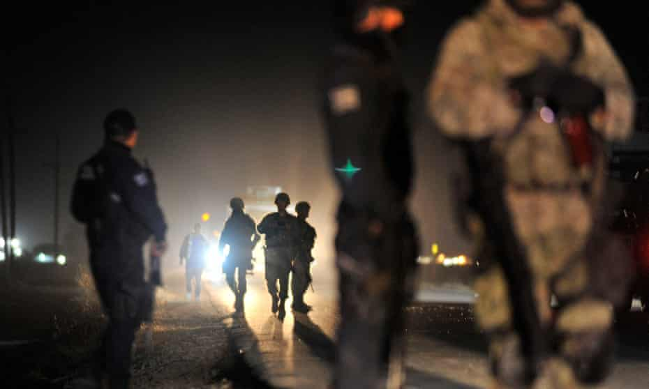 Members of the Mexican army and federal police patrol a crime scene after an organised crime shooting at the Villa Juárez neighbourhood in Navolato, Sinaloa, on 7 February 2017.
