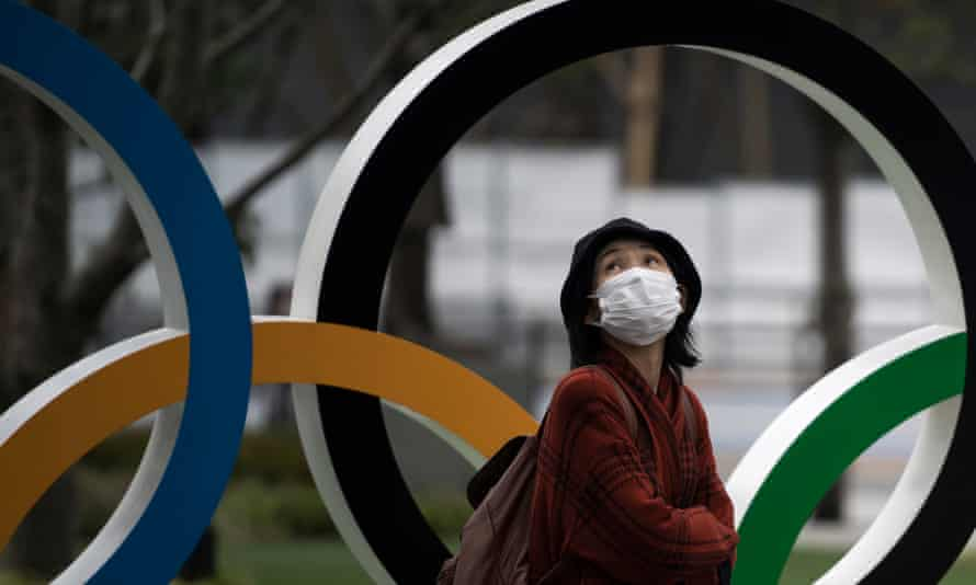 A woman wearing a face mask walks past the Olympic rings in front of the new National Stadium in Tokyo, host city for the 2020 Olympic Games.