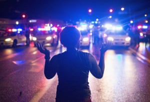 Outrage … a demonstrator marks the first anniversary of the shooting of Michael Brown in Ferguson, Missouri, in 2015.