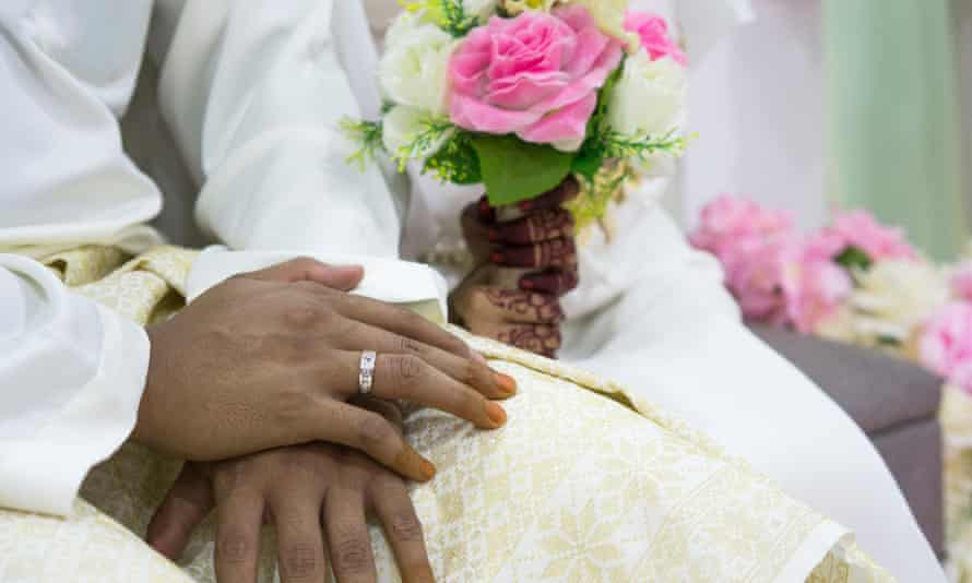 The hands of a bride and groom during a wedding ceremony.