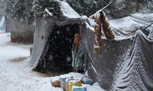 A young girl displaced by fighting in Syria peers out from a shelter as snow falls in Salkeen refugee camp, northern Idlib