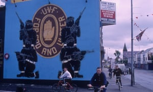 A group of boys cycle past a mural celebrating the  Ulster Volunteer Force (UVF)