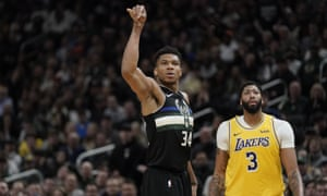 Giannis Antetokounmpo makes a three-point basket in front of the  Lakers' Anthony Davis