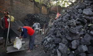 An Indian vendor weighs coal for a customer in Lucknow, India.