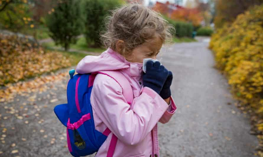 Child sneezing, wiping nose with handkerchief