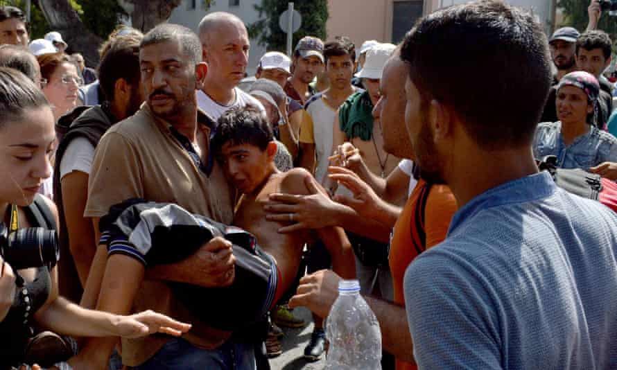 Refugees carry a boy in Mytilene, the capital of Lesbos