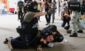A Hong Kong police officer brandishes his pepper spray handgun as he arrests a protester.