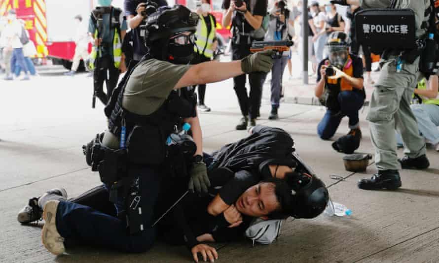 A police officer raises his pepper-spray gun as he detains a man