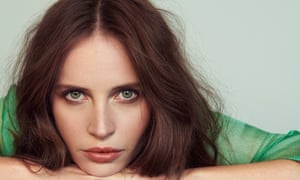 Facial close-up of Felicity Jones , leaning on her hands, in a green top