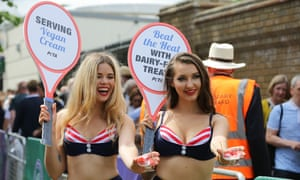 Peta models hand out cups of strawberries and vegan cream to the crowds queuing for Wimbledon.