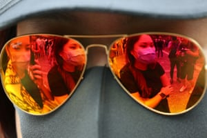 A pair of mirror sunglasses on a mannequin, showing reflection of protesters wearing face masks