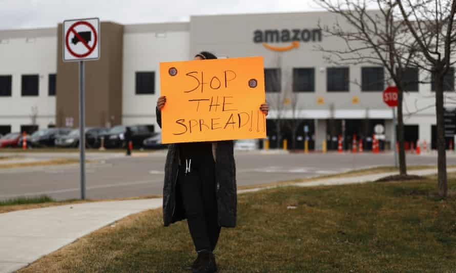 A family member of an employee holds a sign outside an Amazon center in Romulus, Michigan, on 1 April.