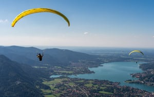 Paragliders enjoy breathtaking views over Tegernsee lake and the town of Rottach-Egern in Bavaria, southern Germany
