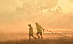 Firefighters defend a property from a bushfire at Hillville near Taree, 350km north of Sydney on 12 November 2019.