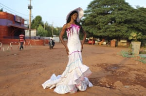 Model Sira Coulibaly in a full-length white dress and hat