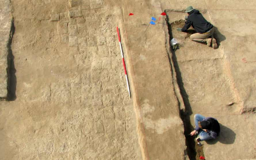 An area of mudbrick paving (left) with archaeologists trying to define the walls of the room next door.