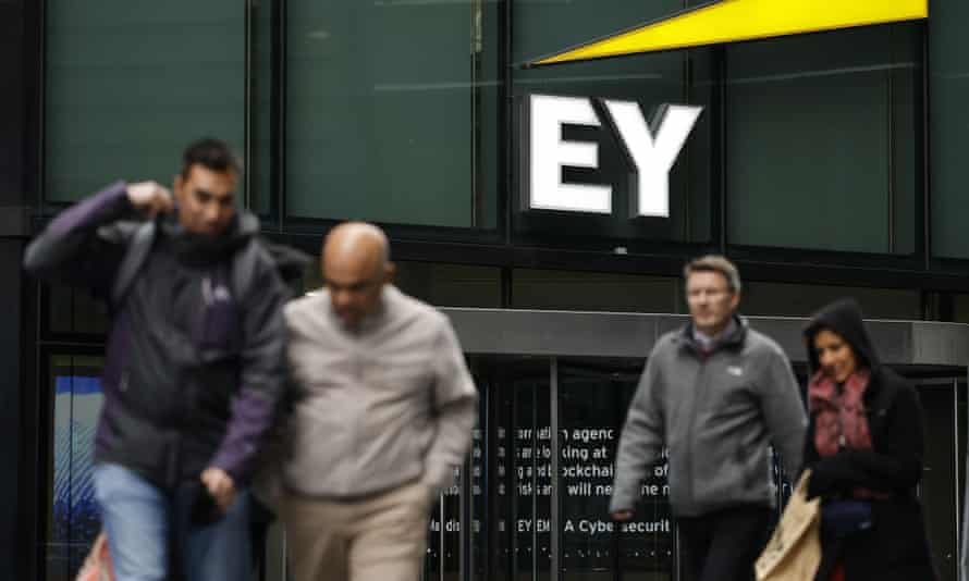 Pedestrians walk past the offices of accounting and auditing firm EY.