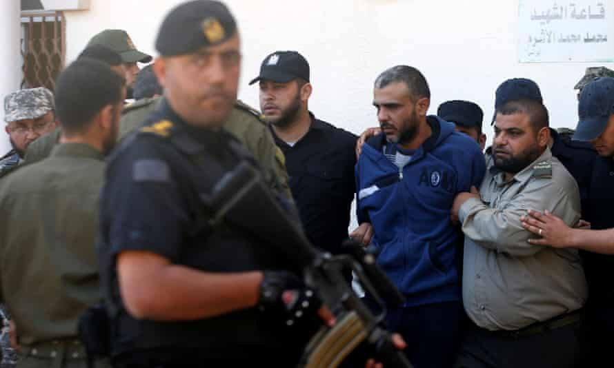 Palestinian security forces escort one of the men convicted of participating in the killing of Mazen Faqha