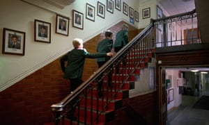 Pupils make their way to class past photographs of former headboys at Altrincham Grammar School for Boys in Altrincham, England.