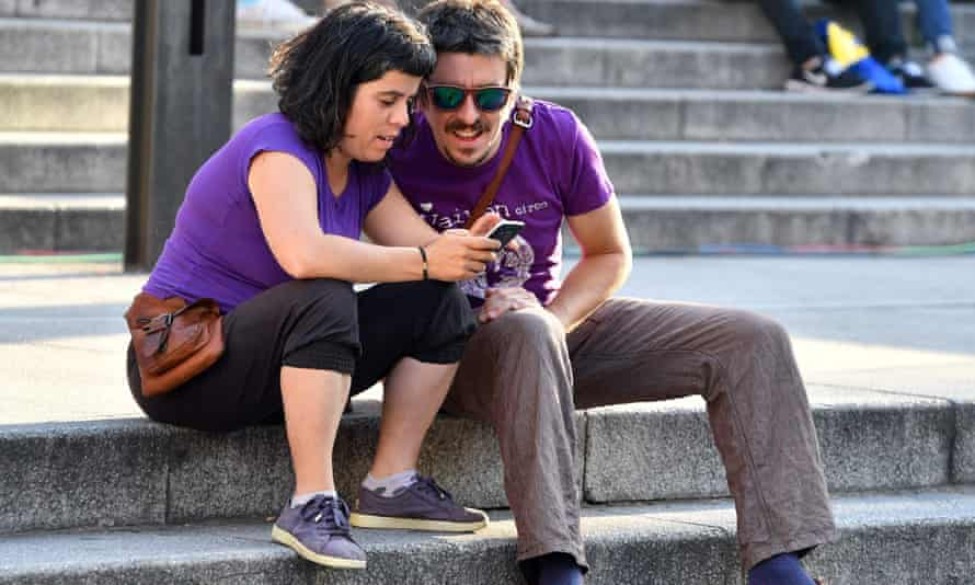 Supporters of left-wing party Podemos check the first exit poll on a mobile phone.