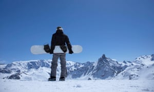 A snowboarder holds their board while surveying the scene