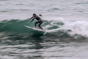 A surfer rides a waves at Caplina beach