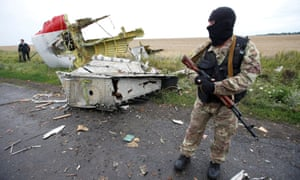 A pro-Russian separatist stands at the MH17 crash site in July 2014
