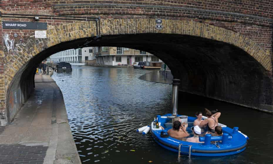 A floating hot tub makes its way along the Regent's canal.
