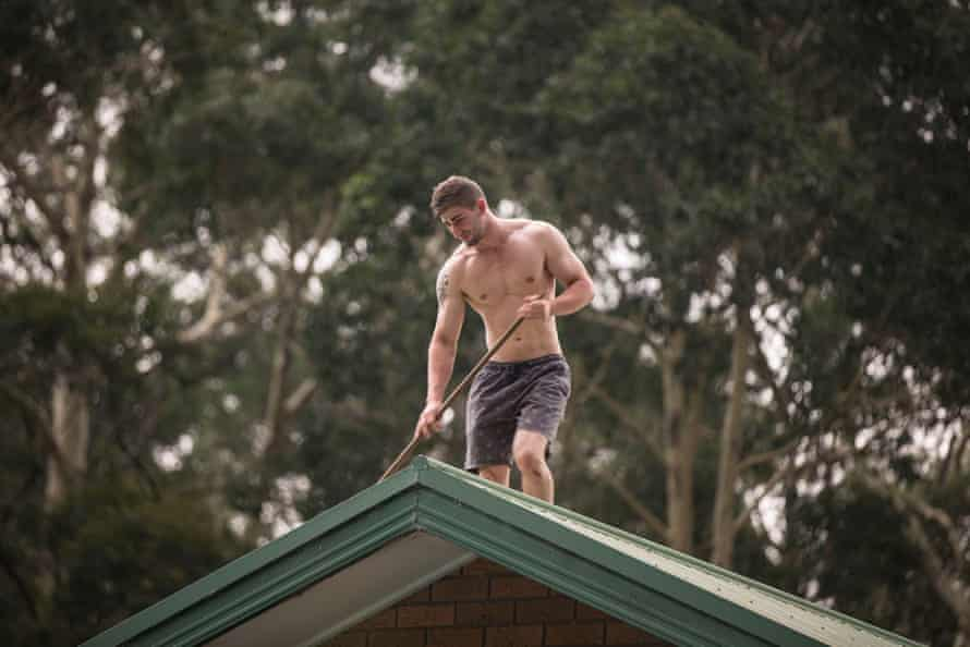 A man sweeps leaves off the roof of his house in St Georges Basin.