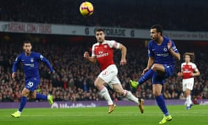 Pedro of Chelsea shoots as Arsenal's Sokratis Papastathopoulos looks on.