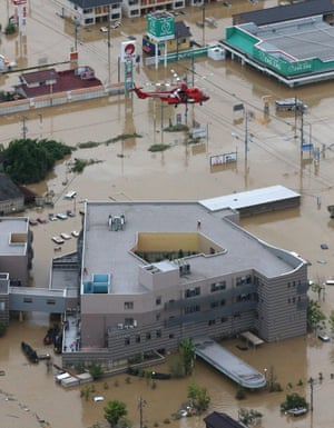 A rescue helicopter over Mabi memorial hospital, isolated by flooding caused by heavy rain in Kurashiki, Okayama prefecture