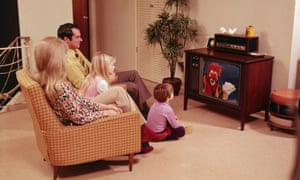a family watch the TV in the 1970s