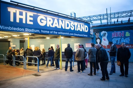 Racegoers queue outside Wimbledon Stadium before it opens for its penultimate meeting.