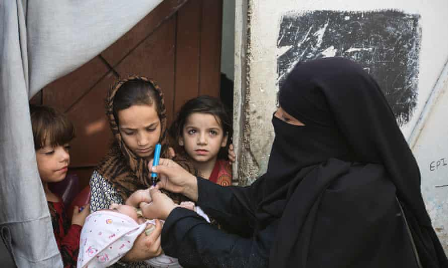 A vaccinator makes a house call as part of Pakistan's campaign to end polio.