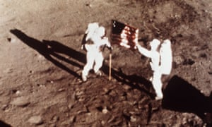 Neil Armstrong and Buzz Aldrin plant the US flag on the moon.
