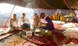 A group of people sitting on Moroccan rugs in a tented area on the beach