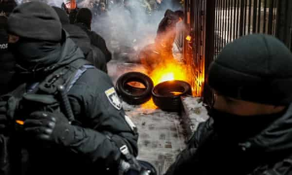 A National Guard officer extinguishes a torch thrown during a rally in front of the Russian embassy in Kiev.