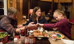Chris Comstock and his wife, Kelly Chick Comstock, and daughter, Adelaide, pray before dinner.