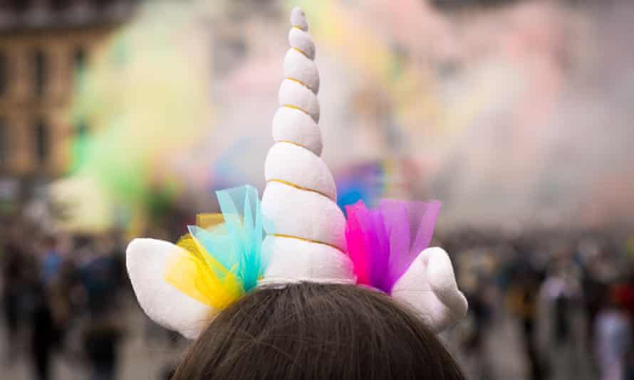 Woman wearing a unicorn horn on her head with bright decorations