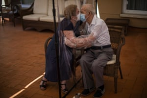 Barcelona, Spain: Agustina Canamero, 81, and Pascual Pérez, 84, hug and kiss through a plastic film screen to minimise the risk of catching coronavirus, at a nursing home in Barcelona